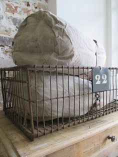 Canvas bolsters and wire basket Industrial Furniture, Furniture Decor, Romantic Shabby Chic, Grain Sack, Displaying Collections, Wire Baskets, Cottage Living, Natural History, Decoration