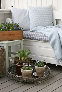 cute--- window seat on porch?  Cute potted plants in wicker basket on porch & wooden container on table.