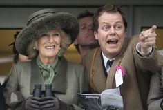 Camilla, Duchess of Cornwall holds her binoculars while her son Tom Parker Bowles points toward the race course at day two of the Cheltenham Festival.