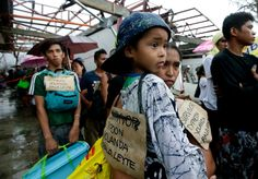 People waiting in line for evacuation wearing signs signifying their status as typhoon survivors, Tacloban, Philippines, 10 November 2013, photograph by AP.
