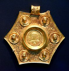 Gold Coin Pendant of Constantine by Osama Shukir Muhammed Amin -- This object is associated with a late Roman emperor , who was at the heart of the changing Roman Empire . This gold pendant is set with a coin of Constantine the Great. The pendant is made in a pierced metalwork technique popular in fine jewellery of the time. The obverse of the coin depicts a bust of Constantine I , who looks to the left. The Emperor wears a radiate diadem and cuirass as well as paludamentum. His right hand…