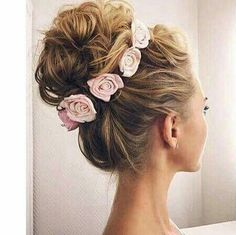 voluminous high bun updo made with curls and crowned with flowers