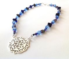 Icy and midnight blue tones - combined with a touch of sparkle - meet the Victorian era with a modern edge in this gorgeous necklace! To create this beauty, I used dark blue floral Murano glass beads, powder blue glass beads, deep blue ceramic beads in geometric shapes, and