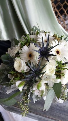 White bluw and greens.  Gerbera, sea holly seeded ecu and dusty miller
