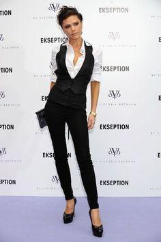 Vicky Beckham le da un aire grunge poniéndose un chaleco negro ajustado encima de la camisa y pantalón pitillo muy ajustado.