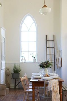Dining Room decor ideas - Rustic, farmstyle dining room. Gothic arched window, farmhouse table, schoolhouse light fixture.