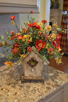 fall decorating idea - fall flowers in a birdhouse