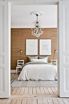 The bedroom in this Swedish apartment caught my eye, the contrast between the honey colored wood feature wall (which is actually wallpaper), the white decorative cornice & ceiling, pale wood floors &