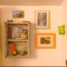 Bathroom arrangement: mementos found while traveling (jar of shells, street art, beach view, foreign coins, hanging glass vase). Shelf made from an old desk drawer.