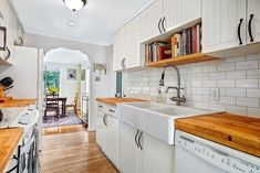 galley kitchen with butcher block countertops and large double bowl farmhouse sink with pull-down spray faucet with floating bookshelf above sink and archway to dining room with cottage style cabinet doors