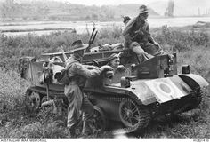 Three unidentified members of the 3rd Battalion, The Royal Australian Regiment (3RAR), rest in their Bren gun carrier during a patrol.  They have pulled up next to a river that runs through an ...
