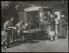 bookmobile, readers choosing books & checking them out, circa 1920s