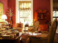 Another view of the Triant living room where oversized windows covered with balloon shades out of Clarence House fabric flank an English 18th century, Chinoiserie red lacquer secretary.