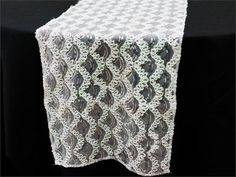 Symphonic Mermaid Scales Sequined Table Runner - White | This ethereal table runner comprises of splendidly sewn glittery silver sequins laced throughout with iridescent thread in an astonishing scale pattern atop white tulle netting. For those ritzy occasions that call for extra glam and glitz, this extravagant piece is a picture perfect choice. The gorgeous scale pattern with sequin accents instantly grabs the attraction and fascination of the bystanders, enhancing the visual appeal of any…