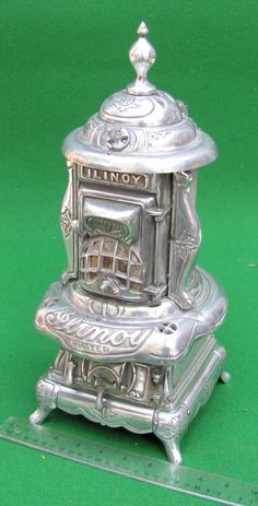 Ilinoy Salesman Sample Wood Stove Heater  This miniature Ilinoy antique parlor stove / heater has a great look to it.  This unusual model or salesman sample is constructed of aluminum and comes apart in sections just like the full size model would.