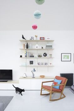 Fiona's cat strolling through her scandi style home with storage shelves giving a pop of colour. | MADE.COM/Unboxed