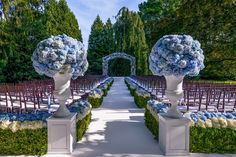 this is a grand outdoor wedding, love the flowers love the color, love it.... its just really big.. i feel this venue is used a lot for this.  i do like the way they added the flowers on top on the box woods defining the aisles of seating.