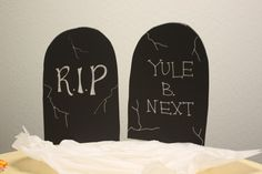 Make your own spooky tombstone Halloween decorations using black foam board! Write on them with white Painters, attach a wooded rod to the back, and stick them in your yard. #HalloweenDecorations
