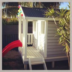 Painted wooden cubby house with bright red slide