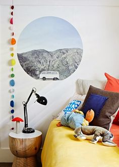 DIY Idea creating a imaginary window in a colourful kids room. Cut a poster with a (dept) view into a window shape (round or arch works best).