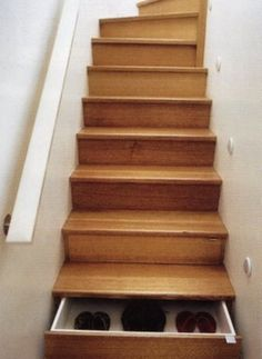 Borrowing from the Japanese tradition, modern woodworking shops have undertaken to produce Tansu-inspired storage in stairs, even when there is no side access at all, as here.