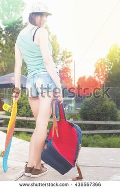 Close-up fashion skateboarder girl with skateboard outdoor near shop. Skatebord at city, street. Cool, Fun Tenager. Skateboarding at Summer