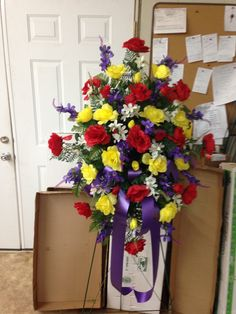 Spring/Summer silk cemetery spray using red and yellow roses, purple and white filler flowers with purple ribbon. 2015.