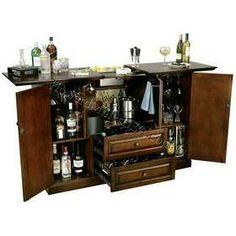 695080 Howard Miller  Cherry Hide- A- Bar Console | Devino Fixed bottle opener and removable catch basket, and the towel bar attached to the inside of the cabinet's center doors. The top surface slides open to reveal a granite work surface and removable ice sink. Features wood stemware rack and one adjustable wood shelf on each side. The center of the cabinet offers additional room for storage. Holds up to 38 wine bottles