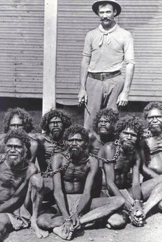 Australian man stands with his new Aboriginals captives.c. 1910s