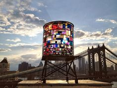 Brooklyn-based artist, Tom Fruin, has built a 25' tall water tank created with 1,000 salvaged plexiglass pieces found around NYC. The piece is illuminated by natural light in day time, and during night a Ryan Holsopple ardunio-controlled light show goes off inside the work. The piece sits atop 20 Jay Street, and you should be able to see it throughout the DUMBO area, and lower Manhattan.