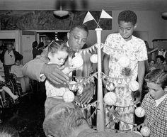 Willie Mays visiting a children's hospital at Christmas.