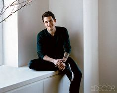 Rock star John Mayer lives in this modern and sleek apartment in New York, decorated by the interior team at Armani/Casa.  John Mayer on the window seat of his New York living room, looking more like a boy next door than a rock star (except this boy next door has a tattoo on his arm)