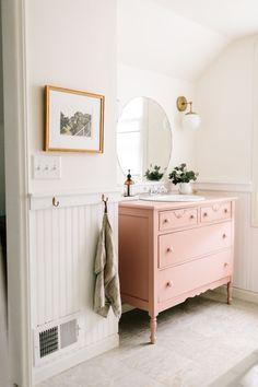 Un meuble ancien repeint en rose pâle dans la salle de bains
