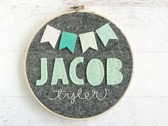 Personalized Hoop Art for Baby Nursery or Child - First and Middle Names with Pennant Banner - Felt and Embroidery - Shower / New Baby Gift This 8 hoop art design has a crisp, classic look! The first name is hand cut and stitched to yarn-dyed linen. Middle name is embroidered underneath. The pennant banner strung across the top adds a simple yet fun addition that is perfect for a nursery, but not too babyish for older children. Linen also available in yarn-dyed steel gray, yarn-dyed…