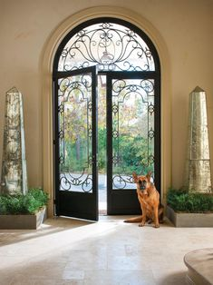 Arched, wrought iron doors flanked by mirrored obelisks open onto a tiled foyer in this grand European house.