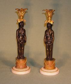 A pair of early 19th century Regency period bronze & ormolu Candlesticks, having unusual leaf scrolled sconces above Egyptian lady stems raised on scagliola column ending on white marble circular bases. Circa: 1820