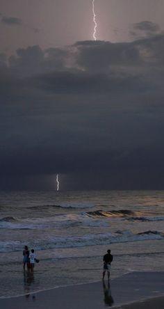 Beachgoers watch as a lightning bolt strikes in the distance off Daytona Beach.