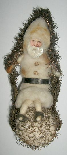 Santa Claus Christmas ornament. Spun cotton & scrap paper Santa with Dresden gold trim, seated on a wire-wrapped & tinsel-garland snowball swing. 13 cm h.