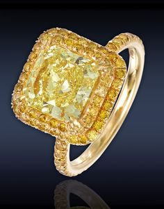 Solitaire natural fancy yellow radiant-cut diamond ring with pave diamond double graduated border and band.