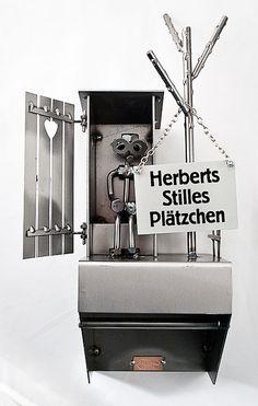 Schraubenmännchen - Mann im Herzeklo mit Klopapierhalter . Schraubenkerl auf einem klassischen Toilettenhaus Dieses historische Toilettenhäuschen wird auch Plumsklo