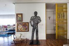 Decoração de apartamento com estilo. No hall porta pantografica amarela, espelho e adornos. No corredor esculturas, obras de arte e quadros.