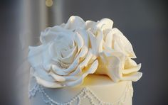 Elegant tall tiered ivory wedding cake, with ivory sugar roses (detail shown here), natural shades monogram and twine feature detail. Venue: Rafferty's Resort, Cams Wharf, Lake Macquarie. May 2014.