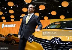 French carmaker Renault CEO Carlos Ghosn poses with the new Renault Scenic model car at the stand of French carmaker during the press day of the...