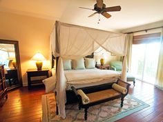Bamboo shades, a cane bench and the draped four poster bed give this master bedroom a British West Indies feel.
