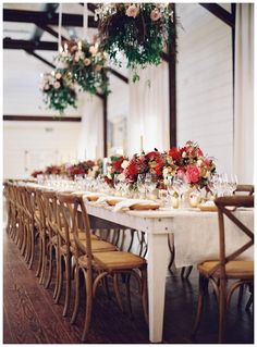 Fall wedding reception. Uncovered white wooden farm table beneath floral chandeliers set with linen runners, wooden X-back chairs, natural wooden chargers and brilliant centerpieces of autumn florals. Event design by Easton Events, florals by Beehive Events. Image by Eric Kelley at Pippin Hill Farm & Vineyards near Charlottesville, VA.