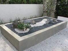 10 Excellent Examples Of Built-In Concrete Planters // This concrete planter full of rocks, pebbles, and plants is like a little desert scene.