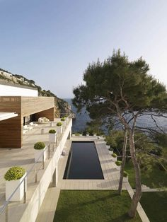 """This contemporary house designed by Susanna Cots is indeed a dream home in an idyllic seaside location in Almunecar, Spain. Dubbed """"Pure White,"""" the wood clad house boasts a bold, solid exterior in contrast to minimalist interiors with a clean aesthetic and an open feel."""