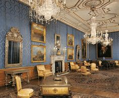 Blue sitting room with gold upholstery and silvered furniture in England.