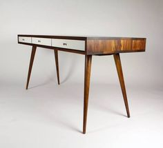 """With the classic Mid Century style, gloss white or walnut drawers, and a 8"""" cable managementcubby in the back, this is the desk for you. Keep your home office"""