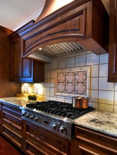 Creamy white tiles frame six colorful patterned tiles in this kitchen backsplash, adding an unexpected punch of color and fun to the traditional space. A large wood range hood makes a grand statement in the kitchen.